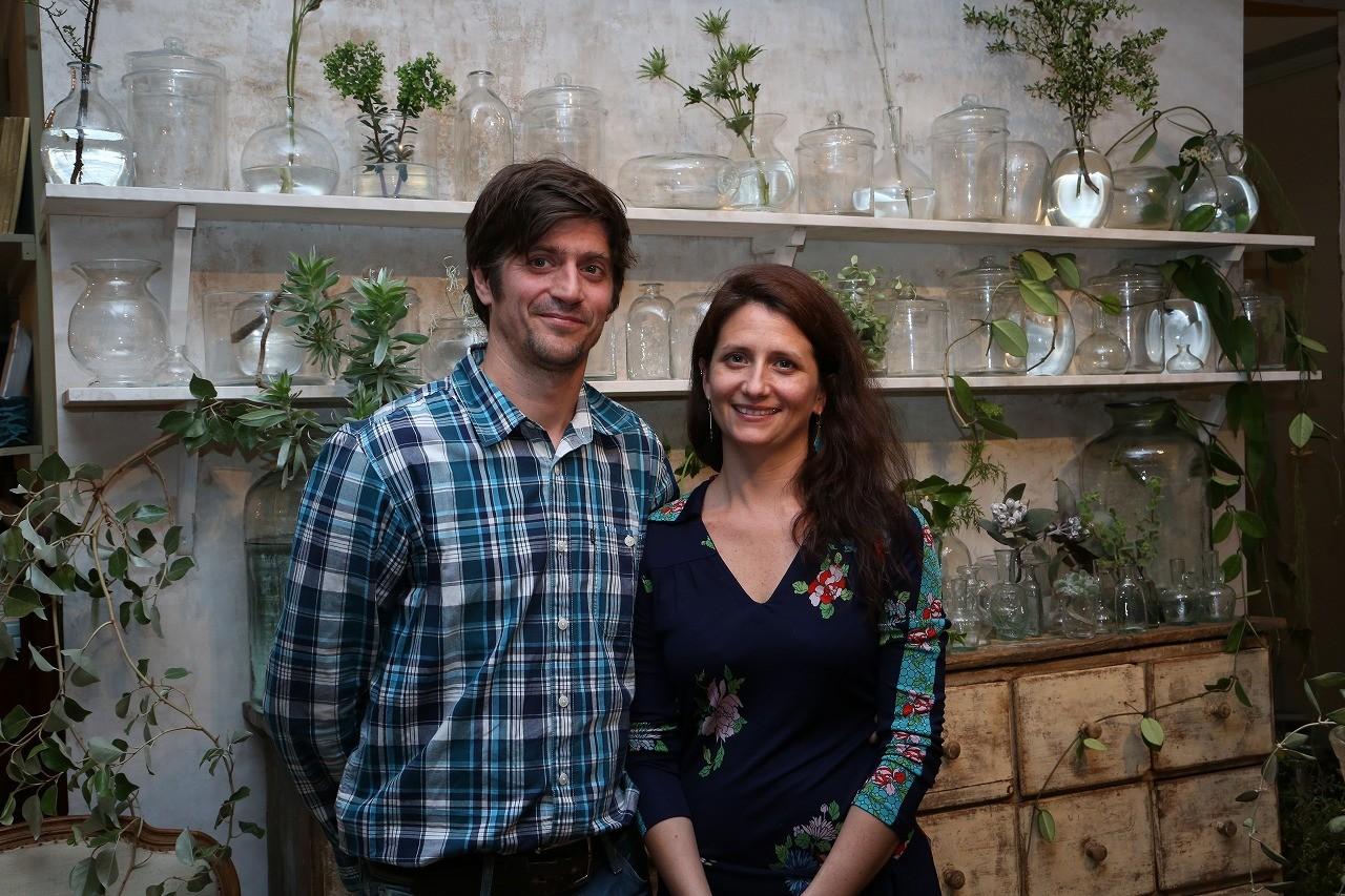 La Soufflerie's creative leaders, Valentina & Sébastien, smile in front of shelves of transparent handblown glass.